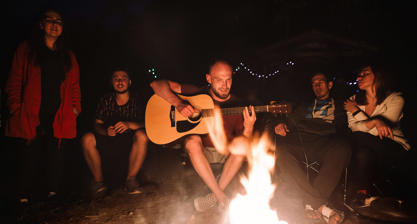Friends travelers chilling at big bonfire, listening to acoustic music
